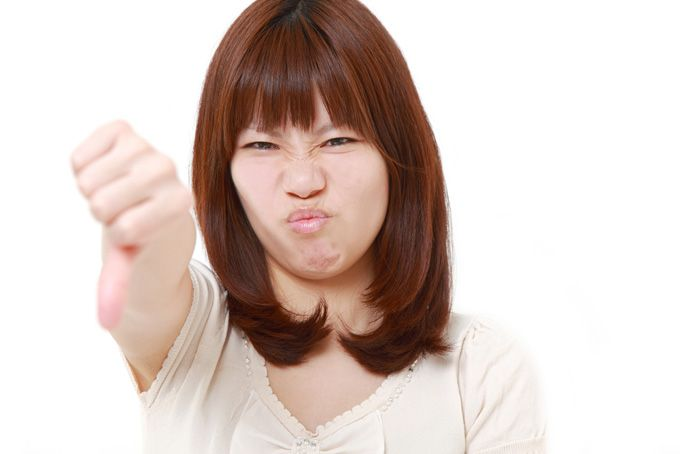 Woman thumbs down, image via Shutterstock
