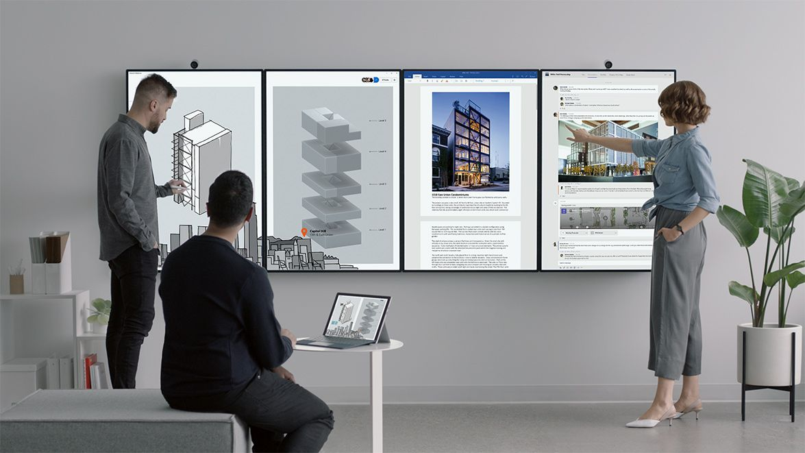 Three people working with four Surface Hub 2 displays